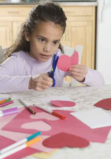 Young Girl Making Paper Valentine Hearts